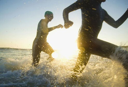 Photo of two people running in the ocean.