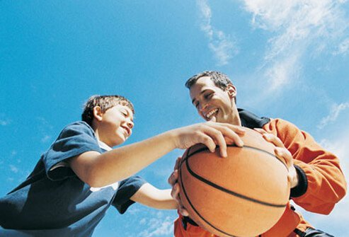 Photo of a father and son playing basketball.
