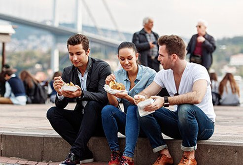 A group of young tourists enjoying street food.