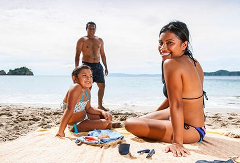 A girl at the beach with her family testing her blood sugar.
