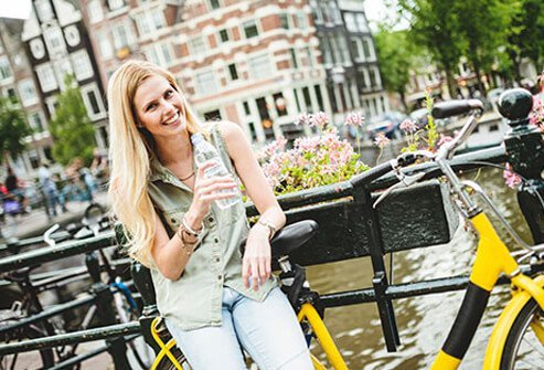 A diabetic woman taking a break from sightseeing to drink water.