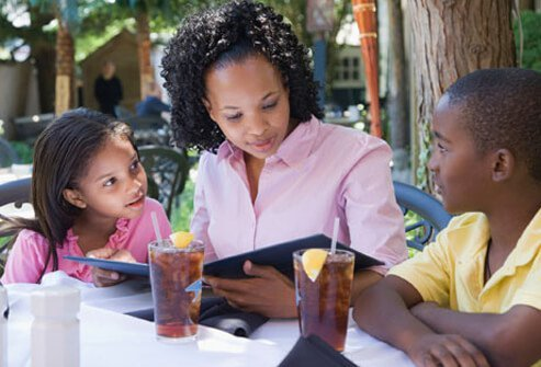 A woman looks at a restaurant menu with her two children.