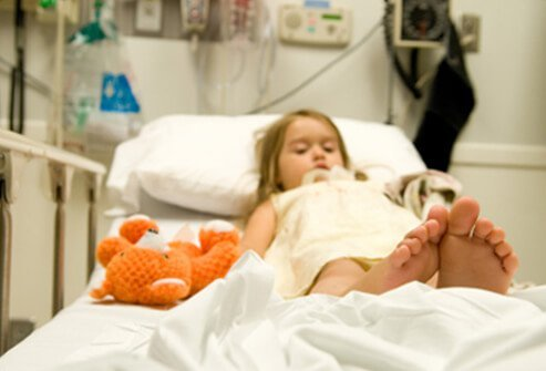 Little girl lying in a hospital bed.