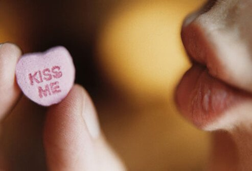 Photo of lips with candy heart.