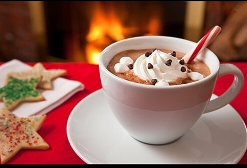 A cup of hot chocolate with whip cream.