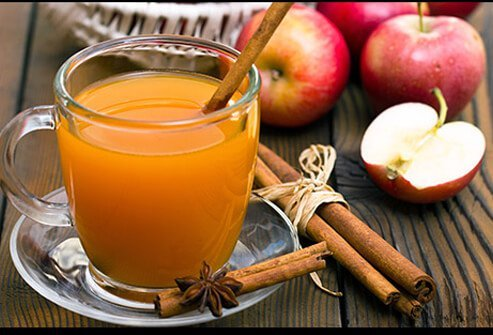 A glass of spiced apple cider with cinnamon sticks.