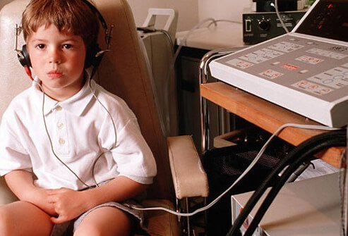 Child getting his hearing tested to check for scarring of eardrums.