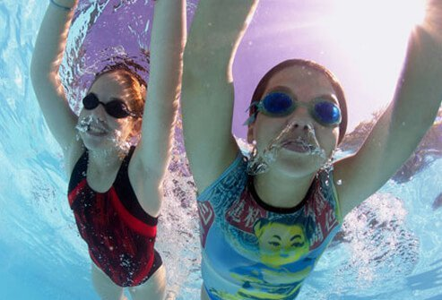 Two girls swimming together, possible cause of swimmer's ear.