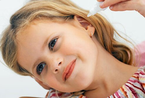 Girl getting ear drops to treat her ear infection.