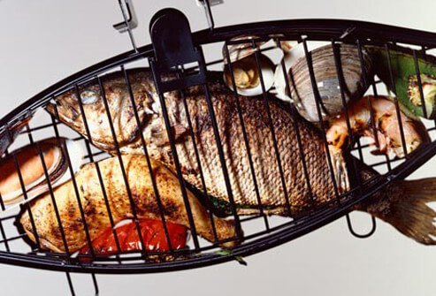 Photo of seafood in grill cage.