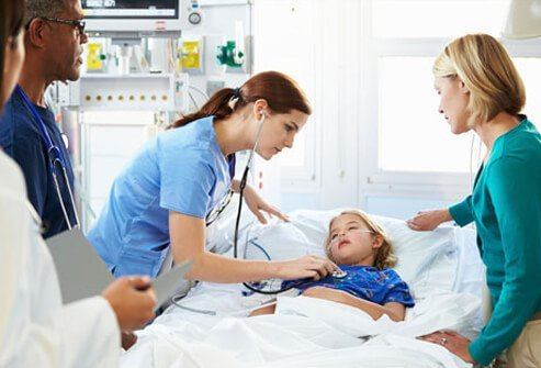 A mother with her ill daughter and medical staff in the hospital intensive care unit.