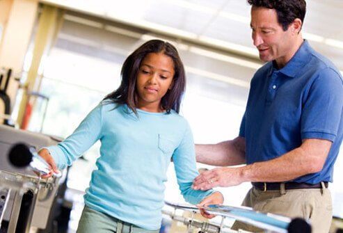 A physiotherapist helping a girl to walk.