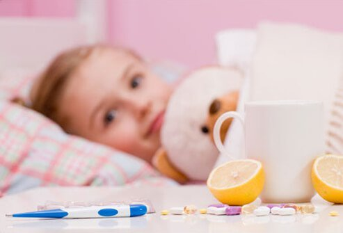 Tea, lemons, medications and a thermometer next to a sick little girl in bed.