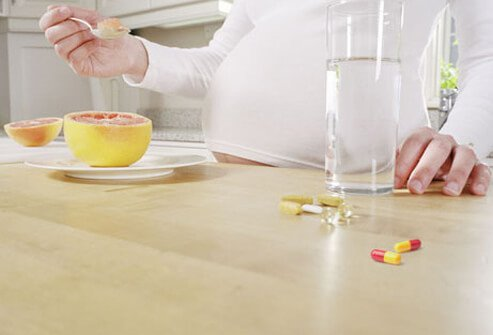 A pregnant woman eating and taking medication.