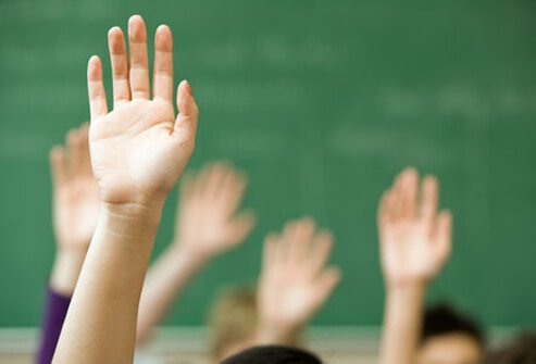 Children raising their hands in class.