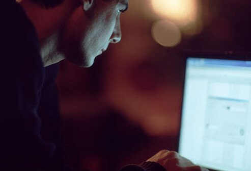 Photo of a man looking at his computer screen at alternative treatments for erectile dysfunction.