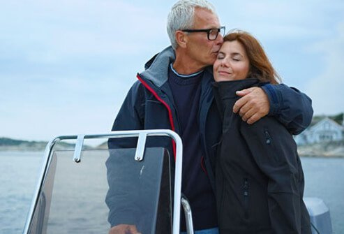 Photo of man kissing and embracing a woman on a boat.