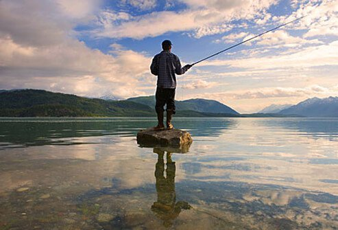 Photo of man fishing in middle of lake.