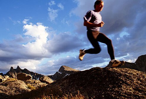 Photo of man running over foothills.
