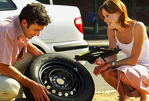 Photo of man changing tire for woman.