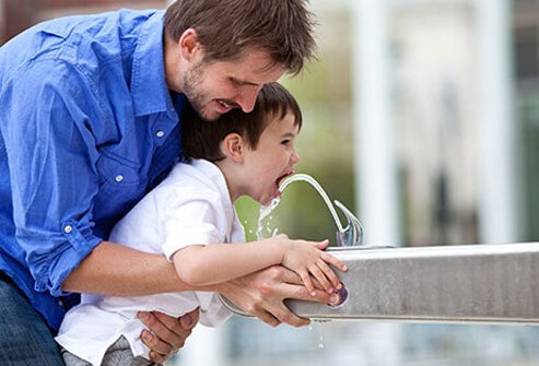 A dad helps his son drink from a water fountain.