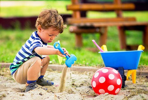 A little boy plays in the sandbox at the park.