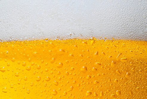 A close up of golden beer with foam head.