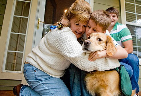 A mother hugging her son and dog.