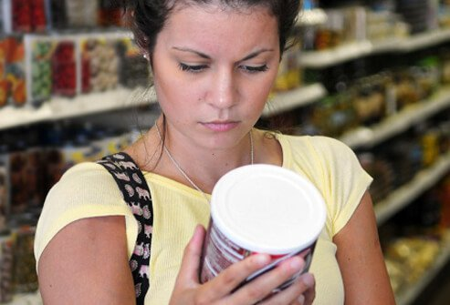 A woman reading the product label in grocery store.