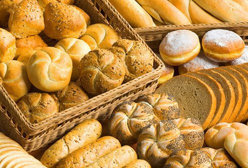 An assortment of fresh breads, rolls, buns, and donuts.