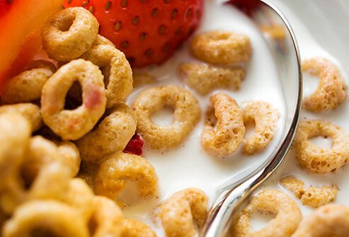 Bowl of cereal, milk, and strawberries.
