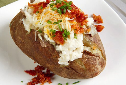 Baked potato with sour cream, cheese, chives, and bacon.