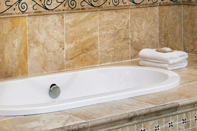 For bathtub and tile, use a sponge to wipe the surface with vinegar, then sprinkle baking soda or non-iodized salt, scrub with a damp sponge, and rinse well with water.