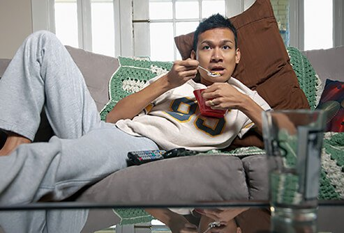 A man mindlessly snacking while watching sports.