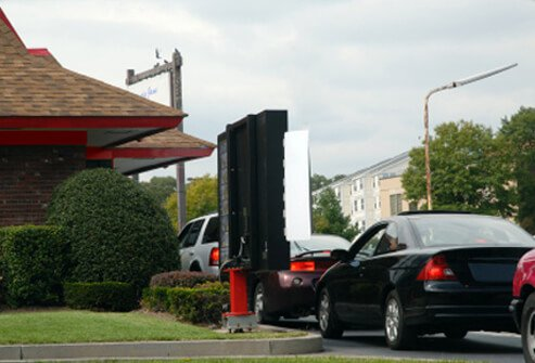 Cars line up at a fast food drive-through.