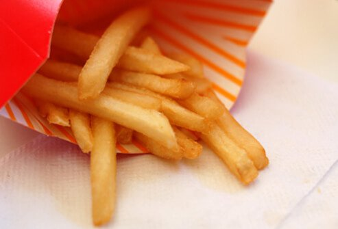 An almost finished container of fast-food fries.