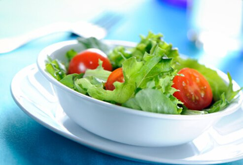 A fresh side salad made of mixed lettuce and cherry tomatoes.