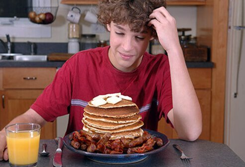 A boy with too many pancakes on his plate questions his breakfast choices.
