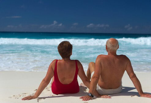 Back view of a senior couple sitting on the beach.