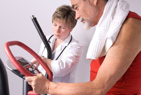 A doctor checks the results of a senior man exercising on a treadmill.