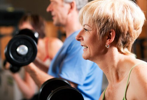 A senior woman and man work out with weights.