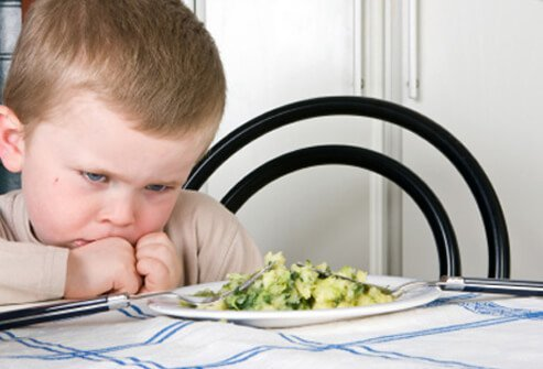 A young boy is not happy about having to eat his meal.