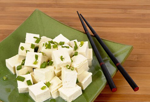 Cubes of fresh tofu garnished with spring onion slices on a plate with chopsticks.
