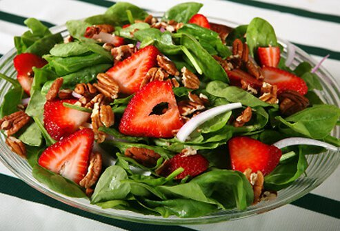 A spinach and strawberry salad served with chopped walnuts.