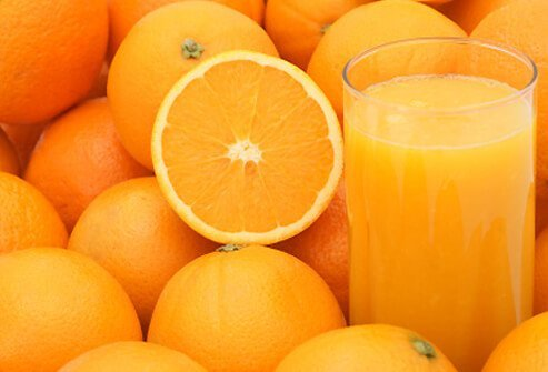 A fresh glass of orange juice amongst oranges.