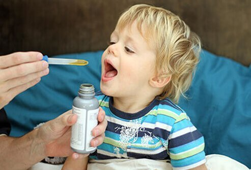 A young boy taking his medicine out of a dropper.