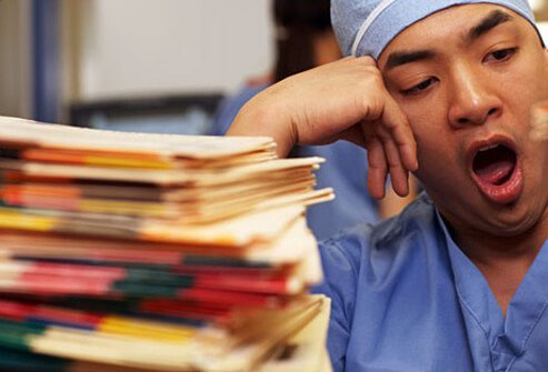 Photo of a nurse yawning over paperwork.