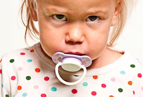 A child upset with a pacifier.