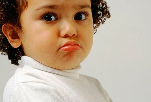 A child pouting in a white shirt.