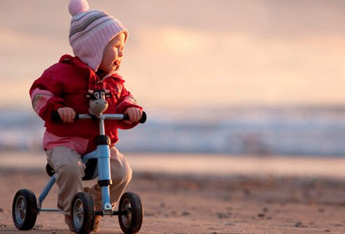 An infant riding her bike.